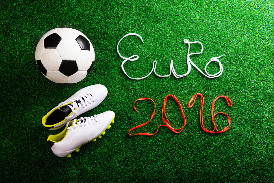 Soccer ball, cleats and Euro 2016 sign made of shoelaces against artificial turf, studio shot on green background.